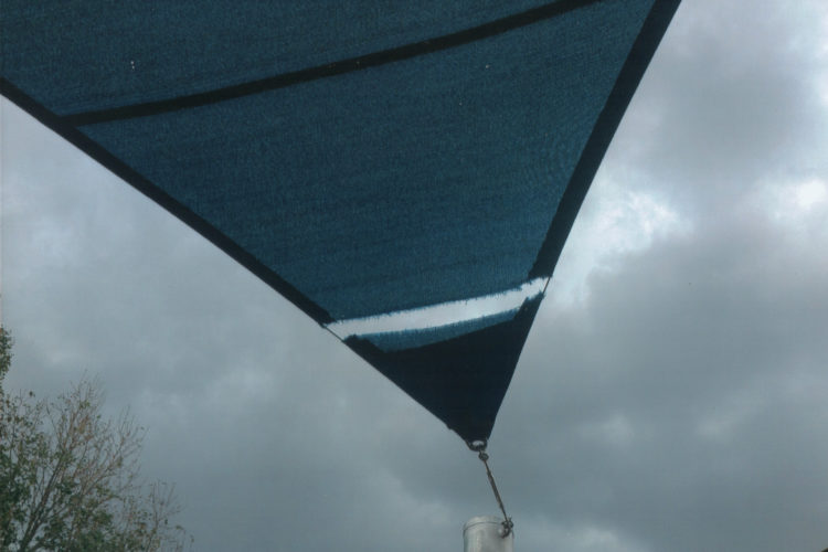 steel cable and shade cloth are a bad marriage for sails under constant tension. The sail naturally moves in windy weather but the steel cable stays stationary and acts like a razorblade